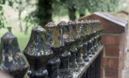 A close up of metal railing with the black paint peeling revealing rust underneath