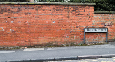 A street sign against a red brick wall next to the road side