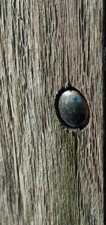 A close up of a metal bolt in the side of a wooden fence post