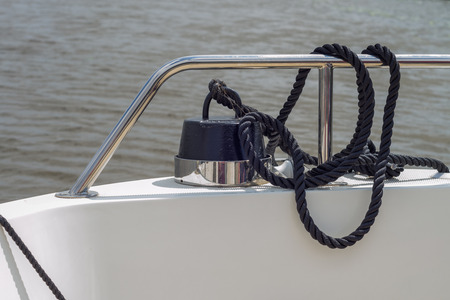A black rope tied to a weight on a boat fastened to the metal railing