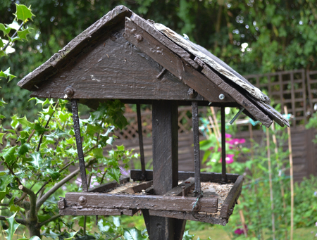 An old brown rickety birdhouse looking weathered and beaten