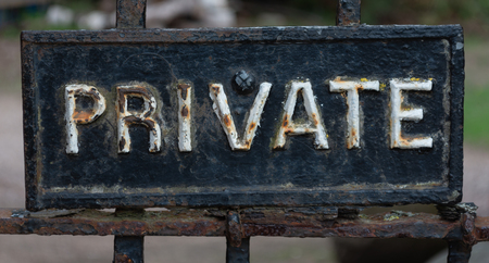 A private sign on a metal railing rusting through the cracked black and white paint
