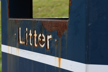 A close up of the litter sign on the side of a rusted blue bin with a white stripe under the letters Banco de Imagens