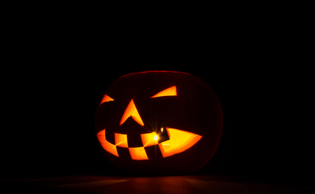 A jack-o-lantern facing off to the side with the light clearly coming from inside giving an eery effect