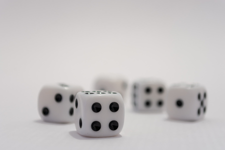A close up of five white dice focused on the number four side of one dice. Numbers two, one, five and six are also visible in the image Banco de Imagens