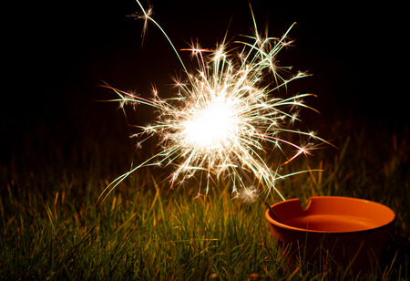 A sparkler burning down inside a plant pot sitting in autumn coloured grass