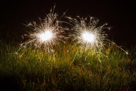 Two sparklers stuck in autumnal coloured grass illuminated the ground beneath