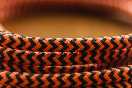 A close up of an orange and black braided cable interwided and wrapped in a circle Banco de Imagens