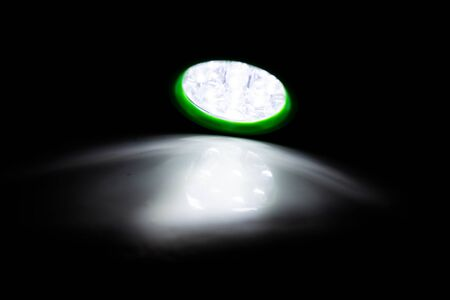 Green LED torch shining a light on a white surface in a darkened room Banco de Imagens