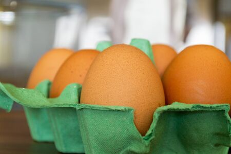 Six eggs sitting in a green cardboard tray viewed from the side and open on a wooden counter top Banco de Imagens - 145365105