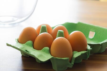 Six eggs sitting in a green cardboard tray open on a wooden counter top. A mixing bowl can be seen in the background Banco de Imagens