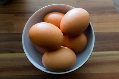 Six brown eggs stacked inside a white serving bowl on a wooden countertop