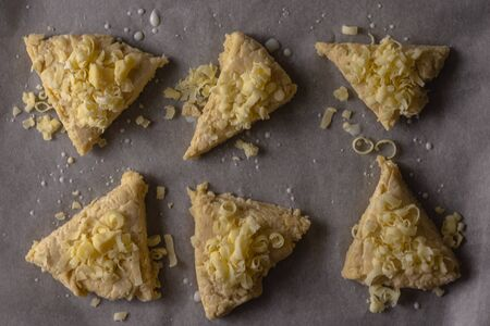 A view of raw cheese scones viewed from the top down. The scones have been cut into triangles and have grated cheese on top Banco de Imagens