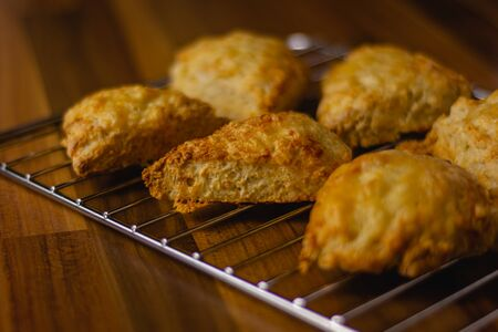Cheese scones sitting on a metal wire cooling rack Banco de Imagens
