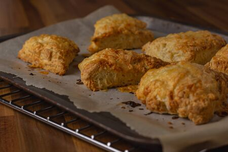 Cheese scones on baking parchment on a metal tray viewed from the side Banco de Imagens