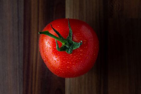 A single tomato viewed from the top down sitting on a wooden work surface