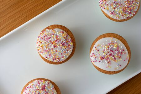 Four iced fairy cakes on a white tray viewed from the top down and covered with multi coloured sugar sprinkles. The white tray is sitting on top of a wooden table