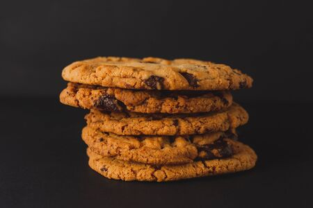 Chocolate chip cookies stacked on a black surface with a black background