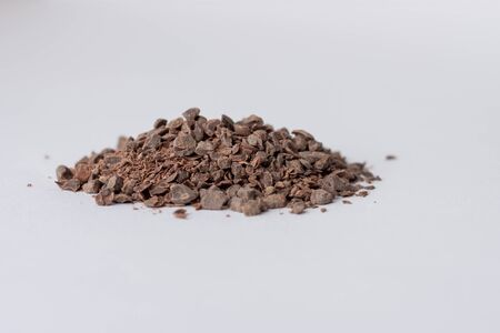 Chocolate granules used for making hot chocolate on a white background viewed inline with the surface