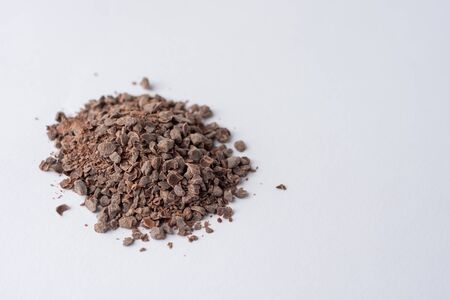 Chocolate granules used for making hot chocolate on a white background viewed from the side Banco de Imagens - 150080737