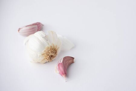 A garlic bulb with cloves pulled out on a white background viewed from the side Banco de Imagens - 147622933