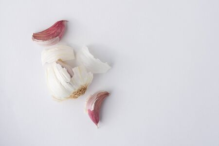A garlic bulb with cloves pulled out on a white background viewed from the top