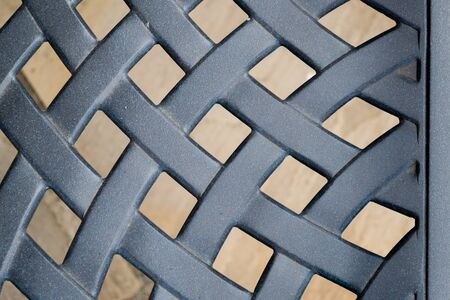 A blue metal lattice pattern with a stone background Banco de Imagens