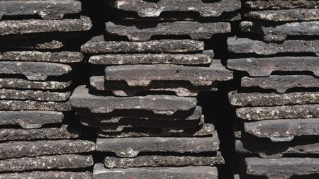 A close up of worn concrete roof tiles stacked into piles