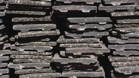 Worn concrete roof tiles stacked into piles