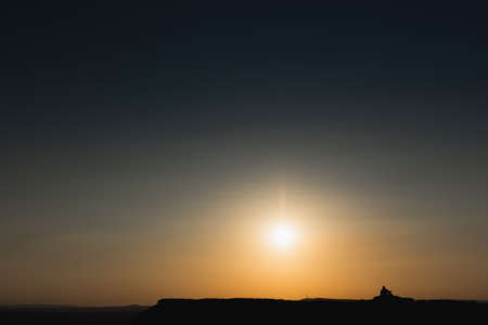 Two people watching the sun go down at Curbar Edge in the Derbyshire Peak District.
