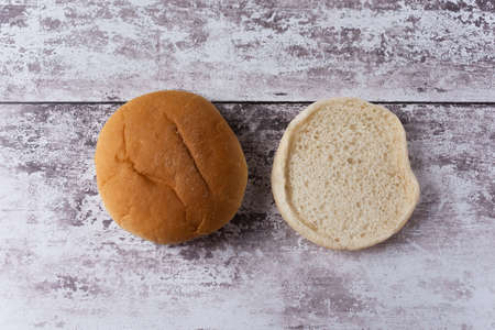 A view of a white burger bun split in half placed side by side and viewed from above Banco de Imagens