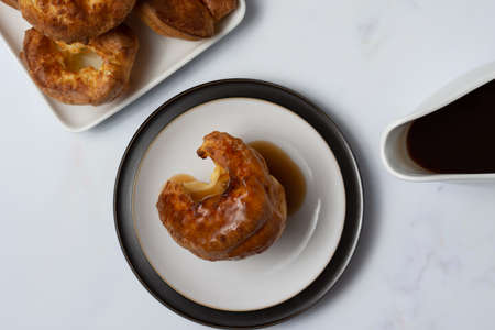 A single Yorkshire pudding viewed from the top covered in gravy and sitting  on a black rimmed plate with a white background and gravy boat in shot