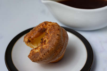 A single Yorkshire pudding sitting on a black rimmed plate with a gravy boat out of focus in the background Banco de Imagens