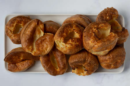 A top down view of Yorkshire puddings stacked on a white tray