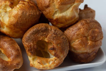 A close up view of a stack of Yorkshire puddings sitting on a white tray
