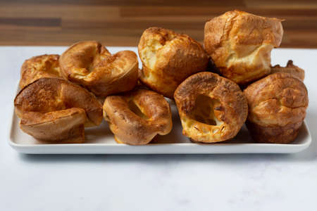 Yorkshire puddings viewed from the side stacked on a white tray