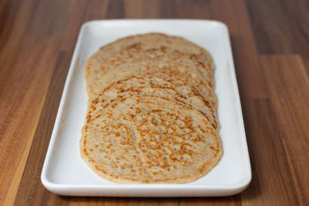 Derbyshire oatcakes viewed from one end on a white platter sitting on a wooden backdrop