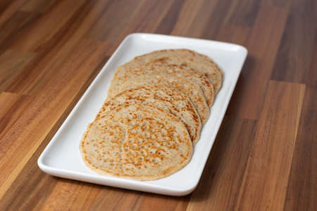 Derbyshire oatcakes on a white platter viewed from an angle with a wooden backdrop