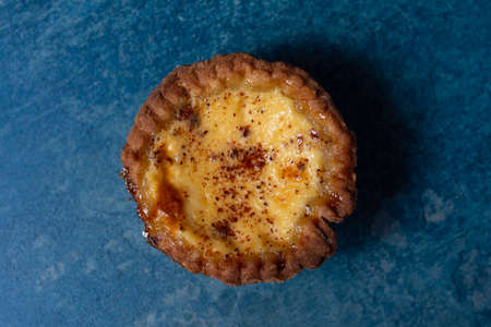 A freshly baked egg custard tart viewed from above sitting on a stone blue background