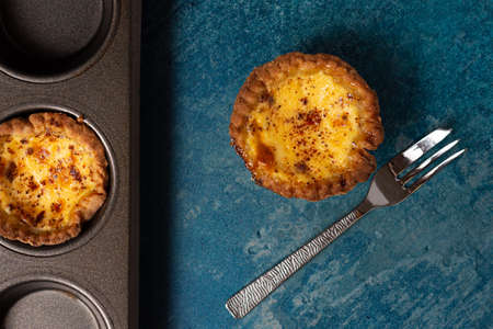 A freshly baked egg custard tart from above with a cake fork laid to the side and a baking tray containing another tart Banco de Imagens