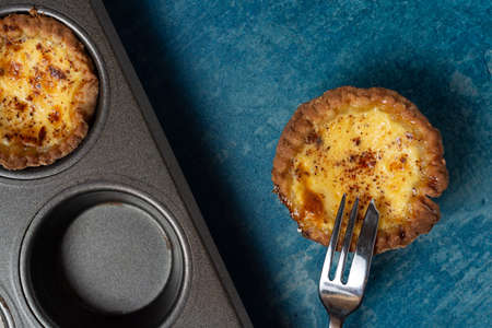 A freshly baked egg custard tart viewed from above with a cake for resting on the tart. A baking tray showing another tart is also visible. On a stone blue background.