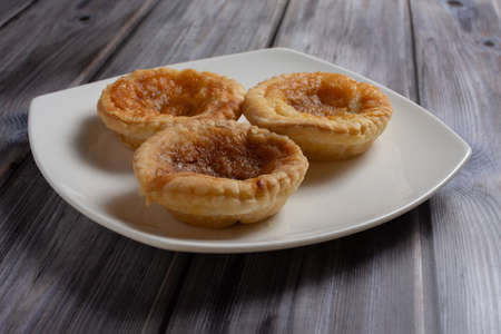 Three traditional bakewell puddings sitting on a white plate viewed from the side