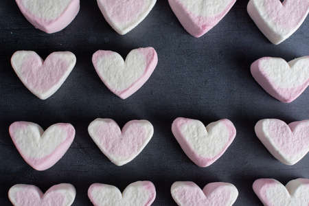 Love heart marshmallows viewed from the top and arranged in rows with a heart missing from one of the rows
