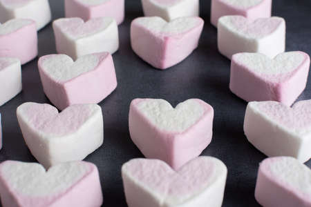 A side view of love heart marshmallows lined up in rows with one missing Banco de Imagens
