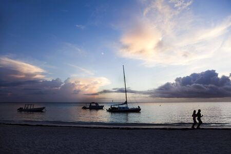 Two people jogging along the shoreline at sunrise. Punta Cana, Dominican Republic. Stock Photo