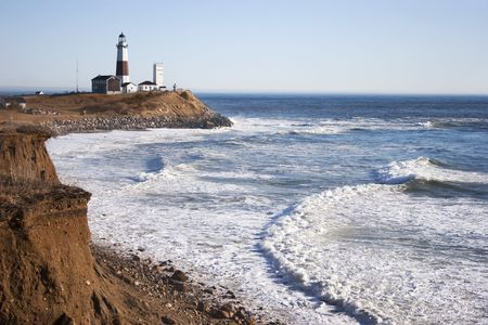montauk: The cliffs, Montauk Point Lighthouse and the turbulent Atlantic Ocean.. Located in Montauk Point, Long Island, New York.