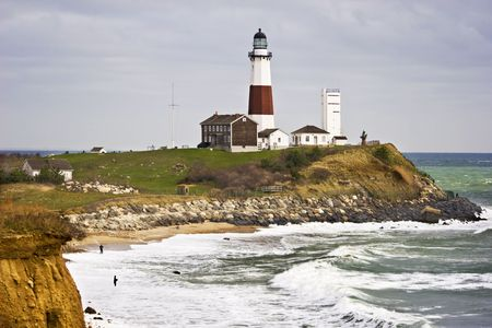 Montauk Point Lighthouse and two fishermen taken from the cliffs of Camp Hero state park  located at  Montauk Point,  Long Island, New York.