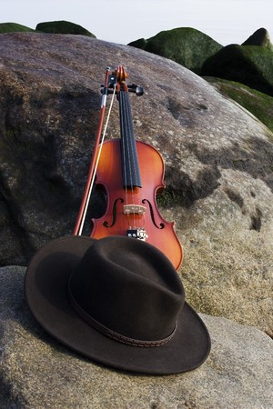 Wide angle view of Violin and cowboy hat lying on a boulder by the Ocean Stock Photo