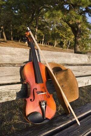 Violin and cowboy hat leaning on a park bench