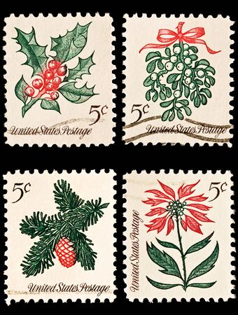 postage stamp: A variety of four Christmas postage stamps. Sprig of conifer, poinsettia, mistletoe and holly
